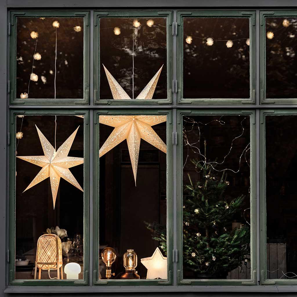 Vindu med julestjerner og julelys.